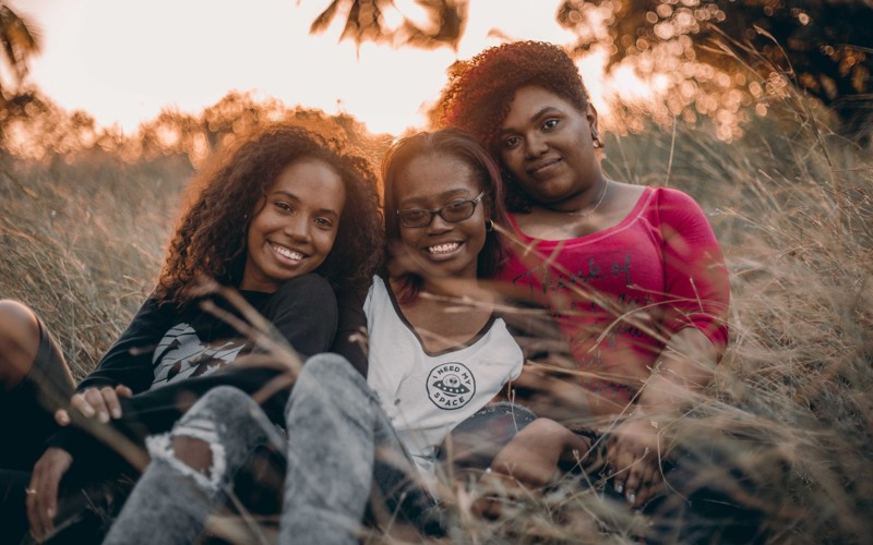 Three smiling women sitting in grass