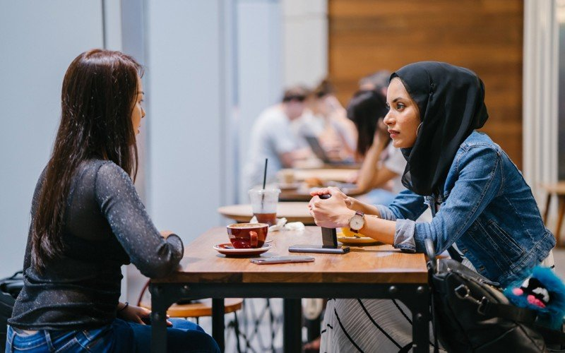 Women sitting at table chatting over a coffee