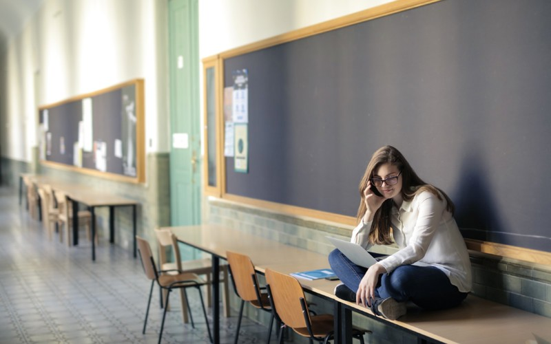 Young woman sitting on a table in a college or school