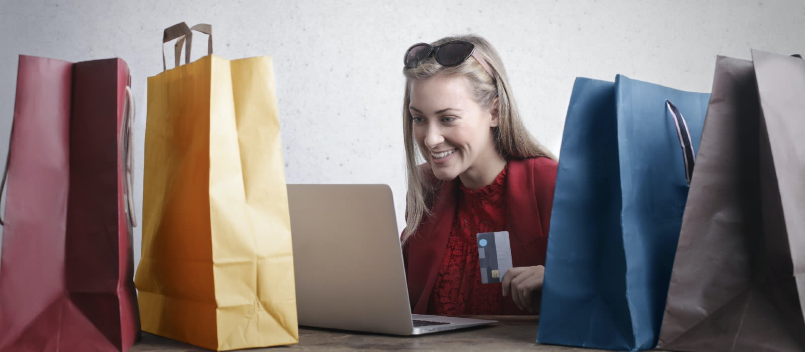 Woman doign online shopping surrounded by shopping bags