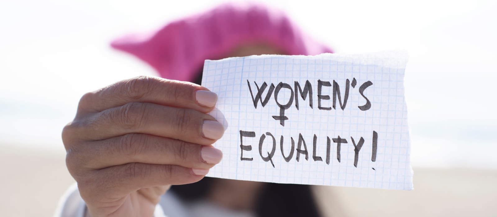 Woman holding paper with Womens Equality written on it